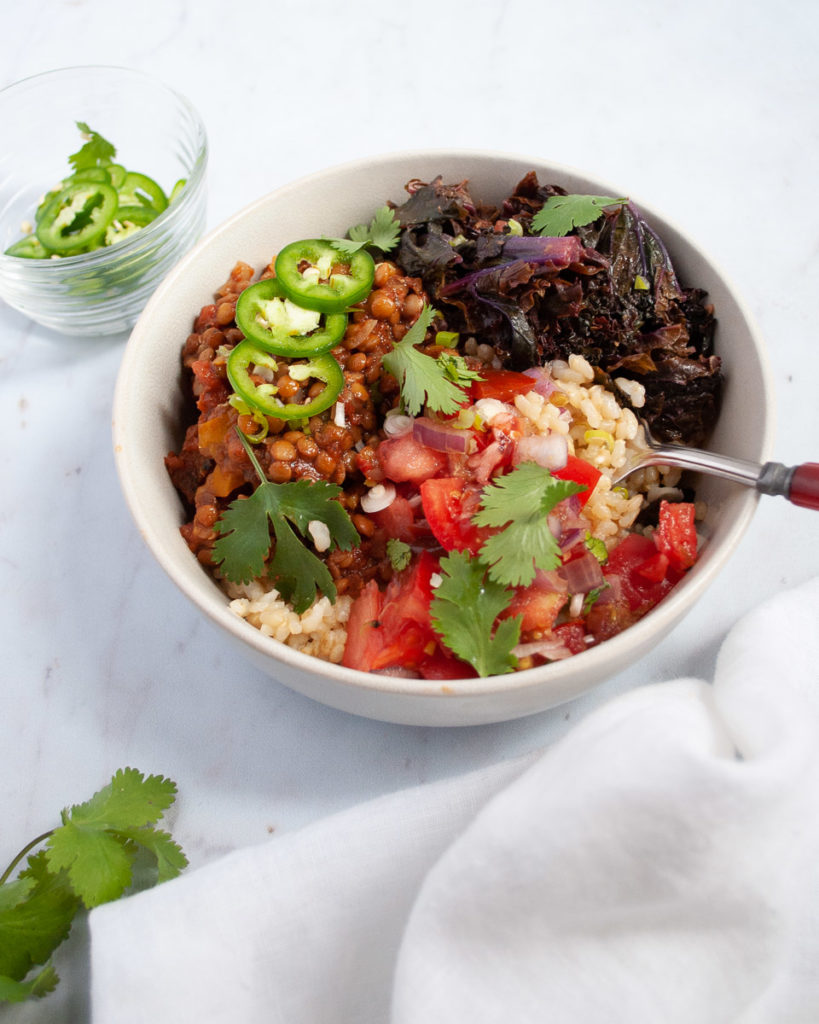 Delicious and fast recipe for vegan lentil taco bowls. Serve the spicy lentils over creamy brown rice and top with sauteed kale, pico de gallo and jalapenos. Yum!